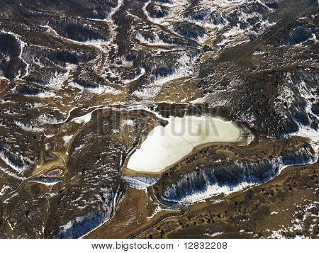 Aerial view of snow covered rural Colorado scenic with lake.