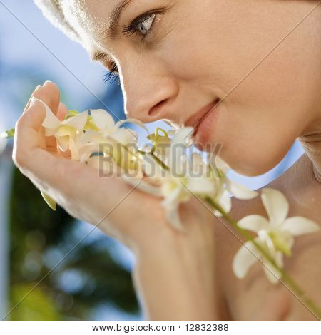 Close up of Caucasian mid-adult woman holding white orchid flowers up to face.