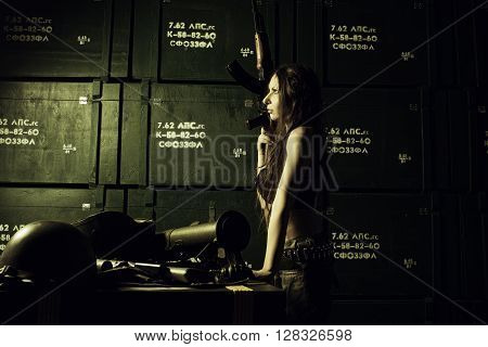Serious girl with ak-47 posing in a storage