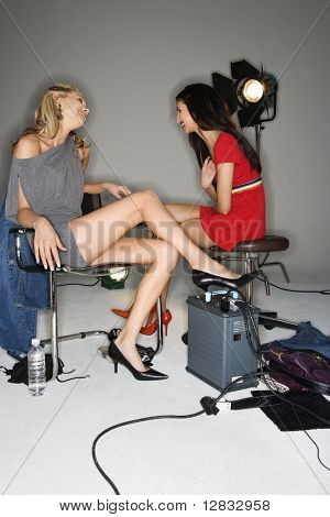 Pretty young women sitting with studio lights talking and laughing.