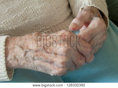 Elderly woman holding and massaging crippled arthritic hand