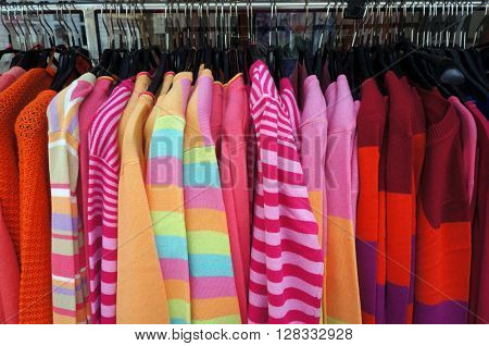 Colorful pullovers on hangers.