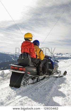 Man and woman riding on snowmobile in snowy mountainous terrain.