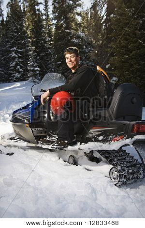 Young man sitting on snowmobile in snow with helmet on lap smiling.