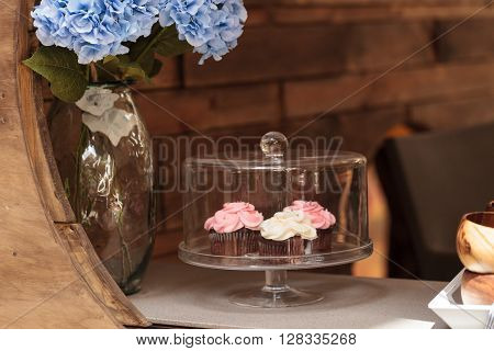 Pink and white cupcakes sit on an open windowsill in a glass domed platter with a blue hydrangea in a vase next to it.