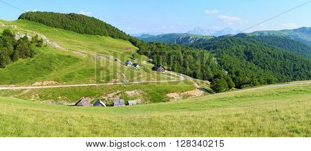 Bjelasica highland idyllic pano view and Planinarski Dom Vranjak Alpine Hut in Montenegro