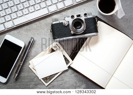 Photographers workspace with camera and computer on a concrete desk