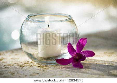 Lit candle in glass bowl and purple orchid beside pool.