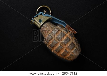 An old rusted hand grenade on a black background poster