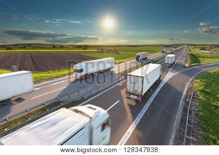 Many delivery trucks driving through agricultural fields. Fast blurred motion drive on the freeway at beautiful sunny day. Freight scene on the motorway near Belgrade Serbia.