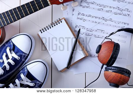 Guitar, headphones, music sheet and gumshoes on wooden surface, top view