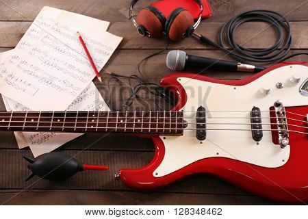 Electric guitar with notes, microphone and headphones on wooden background