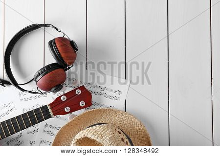 Small guitar, headphones, music sheets and straw hat on wooden surface, top view