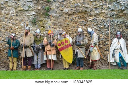 Framlingham, Suffolk, England - May 02, 2016: Men and Women dressed as Medieval men at arms against old wall.