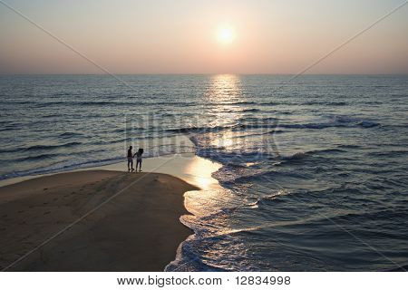Aerial view of couple on beach in Bald Head Island, North Carolina during sunset.