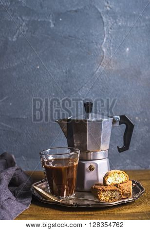 Glass espresso coffee on rustic wooden board, cantucci biscuits and steel Italian Moka pot, grey background, selective focus