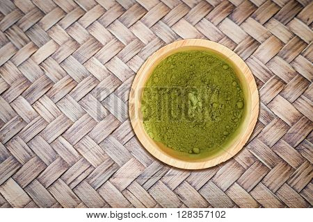 Wooden bowl of green tea powder on bamboo craft texture stock photo