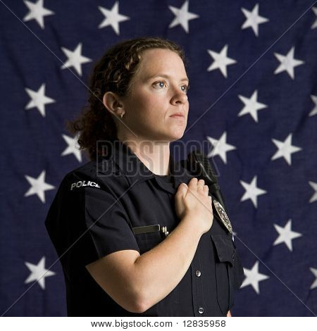 Portrait of mid adult Caucasian policewoman pledging allegiance with American flag as backdrop.