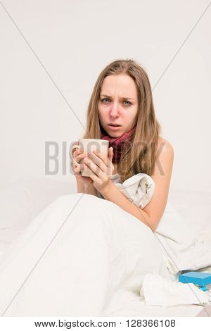 Portrait of upset sick woman with grippe holding cup of hot tea