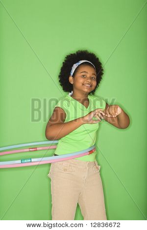 African American girl hula hooping and smiling at viewer.