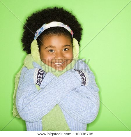 African American girl in winter clothing with arms crossed smiling at viewer.
