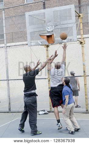 New-York City USA - May 04 2015: young men in action playing basketball in the street