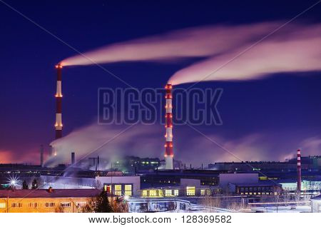 Smoking chimneys and industrial plant engineering plant at night. Top view