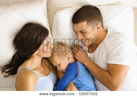 Caucasian mid adult parents with toddler son sleeping in bed.