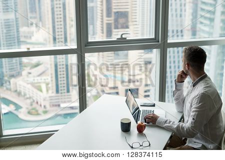 Businessman in a modern office looking through the window.