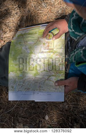Map and compass in sunspot on the lap of a hiker who sitting on the ground. Route planning.