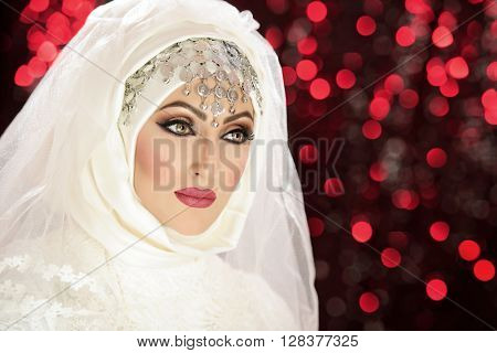 Portrait of a beautiful asian indian model in bridal costume and traditional jewellery and makeup poster
