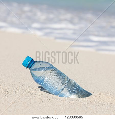 Plastic Bottle Of Water In Sand On Tropical  Beach