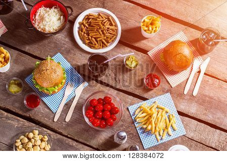 Burgers on sticks and tomatoes. Food and spices on table. Pile of fries and crackers. Food prepared for a picnic.