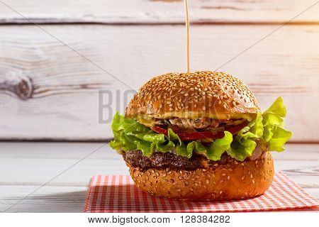Big burger on a stick. Burger laying on checkered napkin. Beefburger on white wooden table. Tastiest dish in bistro menu.