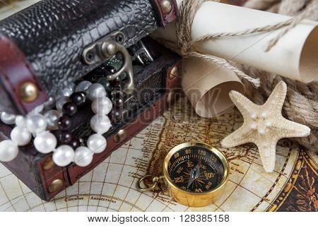 Treasure chest scrolls of paper compass starfish and the ship's rope located on the background of old map