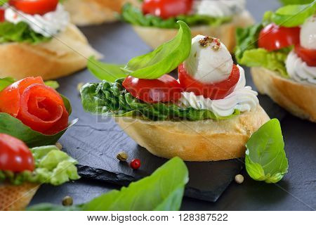 Delicious cold starters: Slices of baguette with cherry tomatoes, mozzarella, cream cheese, olive oil and basil leaves