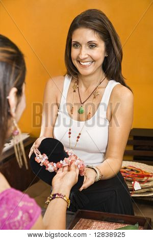 Sales clerk showing necklace to woman shopper in boutique.
