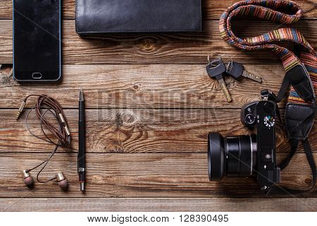 Travel concept - headphones, camera,  sketchbook, purse, pencil and keys on wooden background. Flat lay top view photo with copyspace in center.