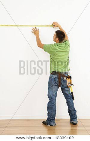 Man wearing tool belt measuring interior wall.