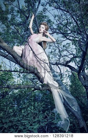 Lovely young lady wearing elegant white dress with roses standing on the tree in wood