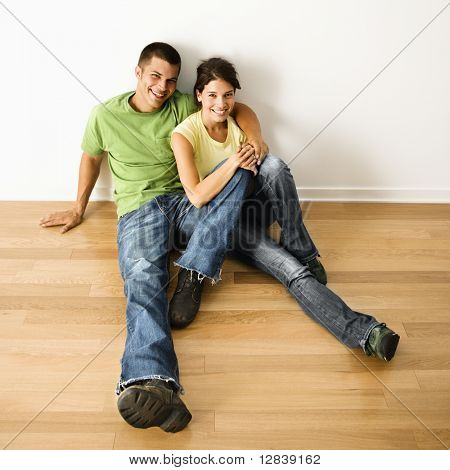 Attractive young adult couple sitting close on hardwood floor in home smiling.