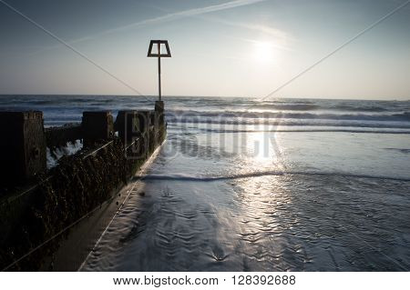 A breaker with the waves coming in at sunrise at Swanage, Dorset