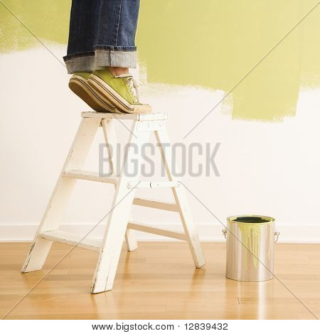 Legs of woman standing on tiptoe on stepladder with paint can and painted wall.
