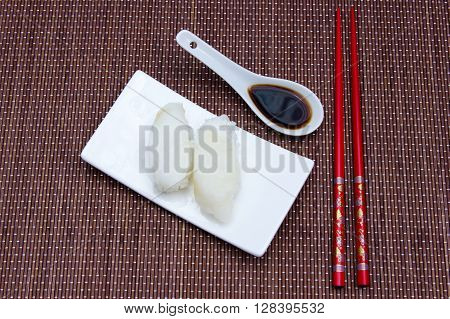 Nigiri with halibut on a placemat bamboo seen from above
