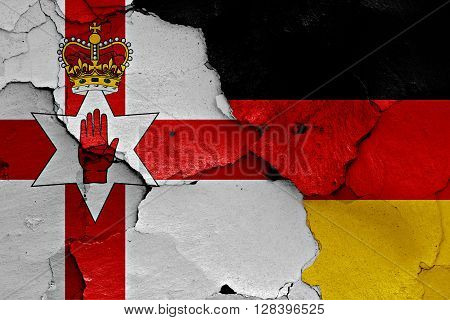 flags of Northern Ireland and Germany painted on cracked wall