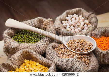 Hessian Bags With Dry Peas, Chick Peas, Red Lentils, Wheat And Green Mung On Kitchen Table