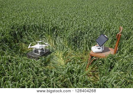 Russia Poltavskaya village - May 1 2016: Quadrocopters on a plastic box among the wheat stalks and control panel with a clipboard on a chair. Preparation quadrocopter to fly.