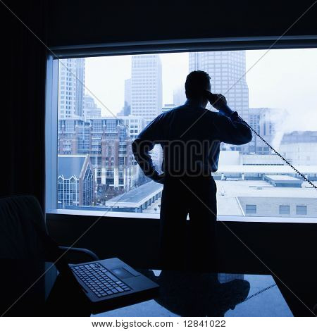 Middle-aged Caucasian male on phone in office with skyline in background.