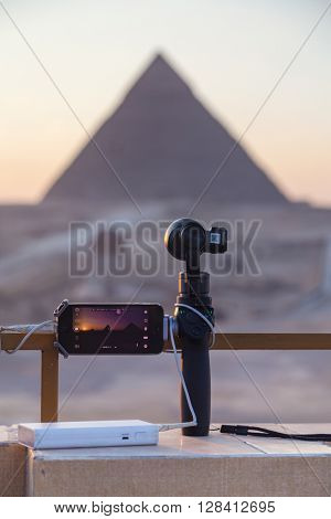 CAIRO, EGYPT - FEBRUARY 2, 2016: iPhone on Osmo device and battery pack set up to record timelapse of The Great Pyramid of Giza at sunset.