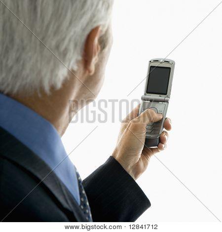 Achteraanzicht van de Kaukasische midden oude mens kijken naar mobiele telefoon.